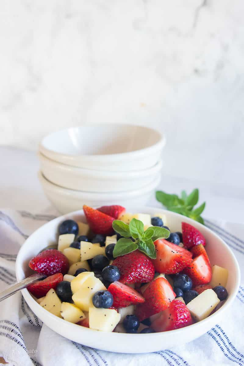 A summer salad with strawberries, blueberries, and apple in a white bowl.