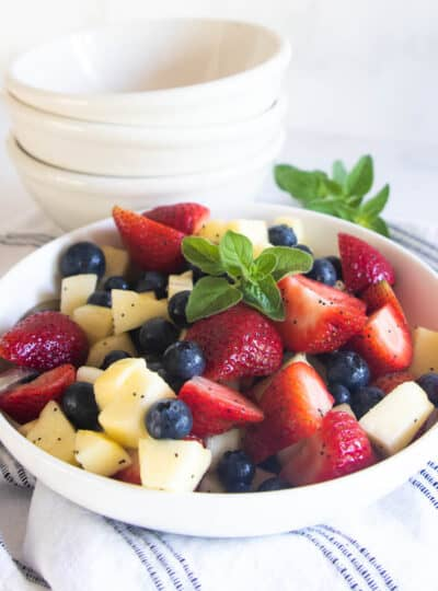 A summer salad with strawberries, blueberries, and apple in a white bowl with a poppy seed dressing.