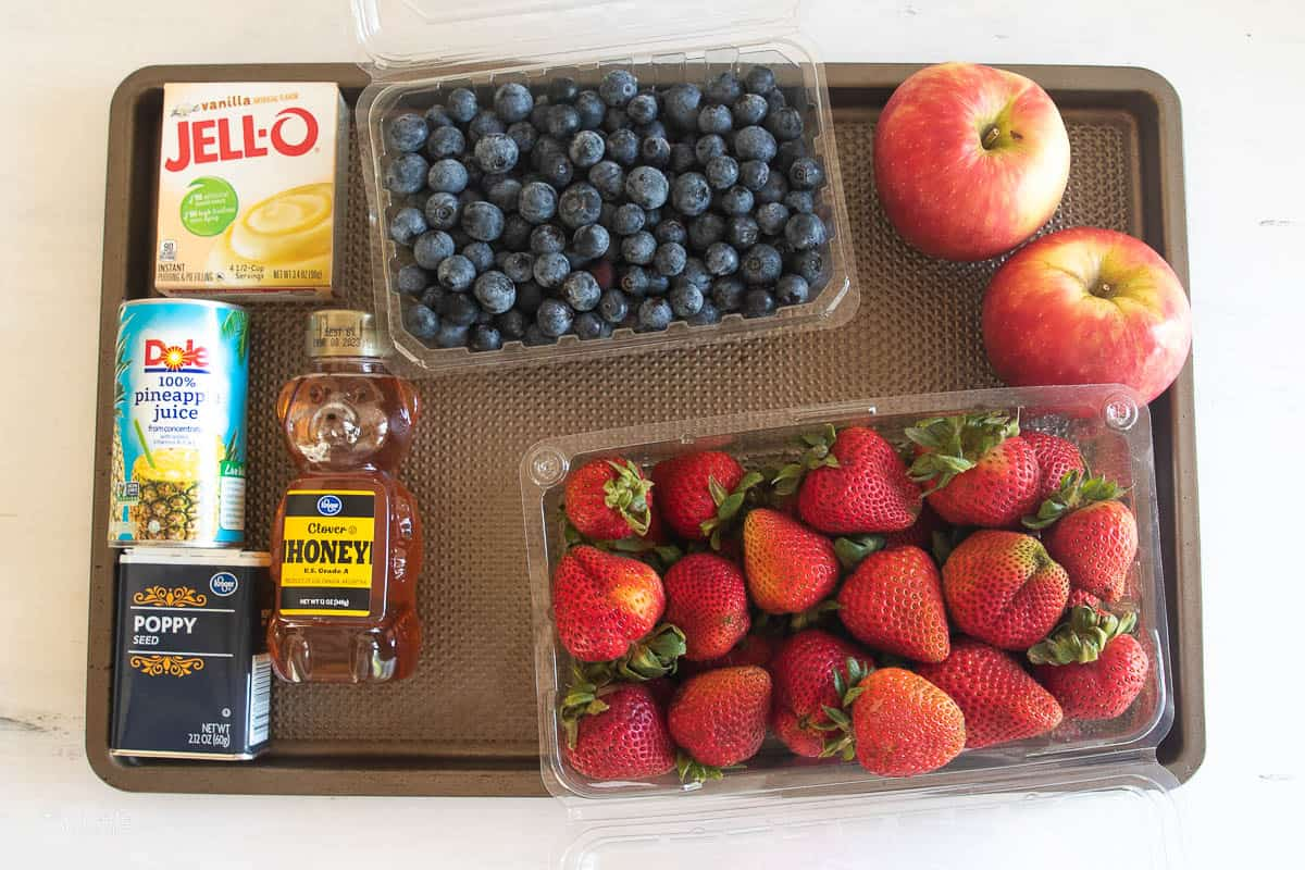 A tray with blueberries, strawberries, apples, jello mix, pineapple juice, honey, and poppy seeds.