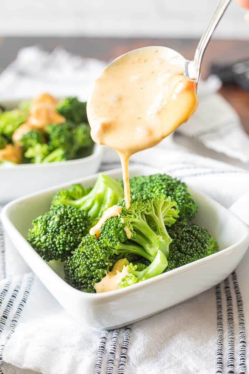 cheese sauce drizzled over broccoli