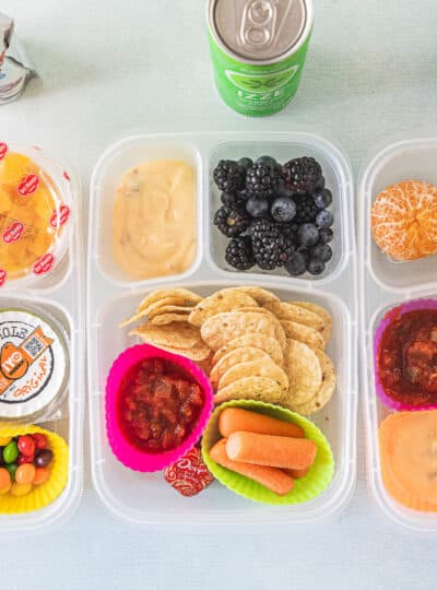 Homemade lunchable with tortilla chips, berries, cheese sauce, and carrots.
