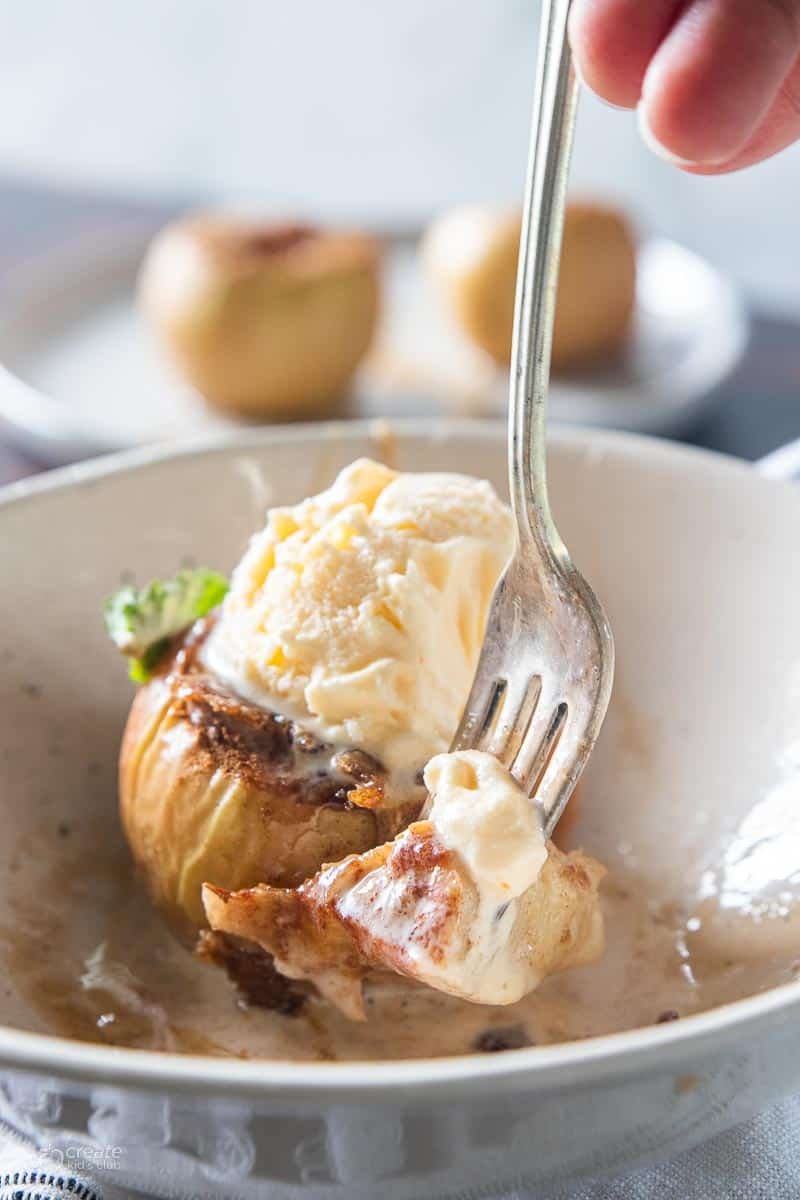 A fork with a bite of air fryer baked apple that's in a bowl with ice cream on top.