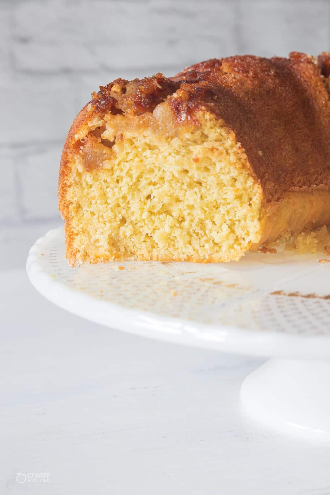 half loaf of gluten free apple cake on cake stand