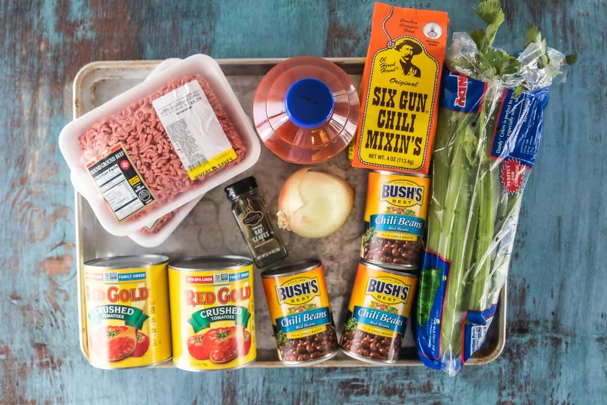 Ingredients to make slow cooker chili for halloween including crushed tomatoes, chili beans, and ground beef.