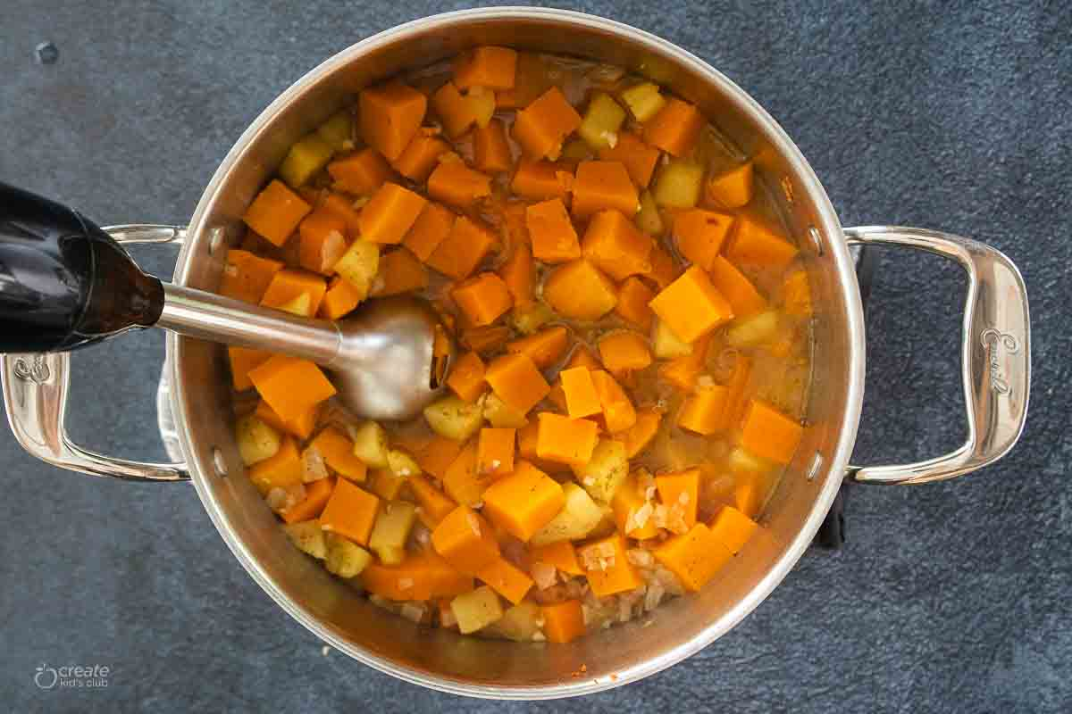 immersion blender in stock pot filled with butternut squash