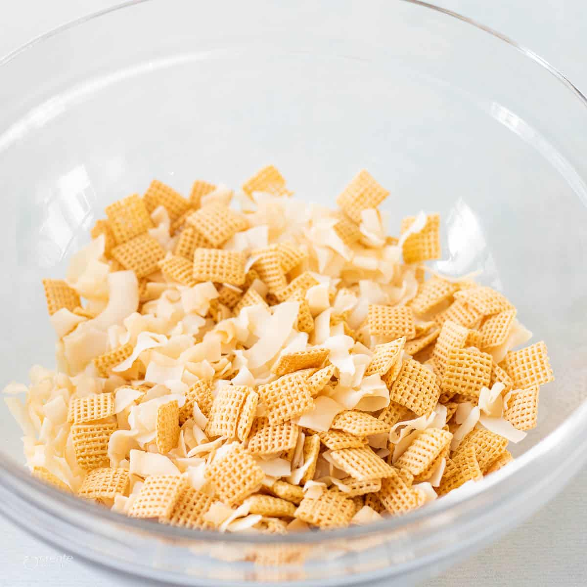 Chex cereal and coconut shreds in mixing bowl