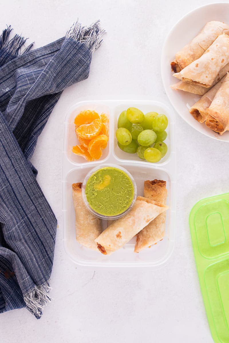 taquitos packed with guacamole in a lunch container.