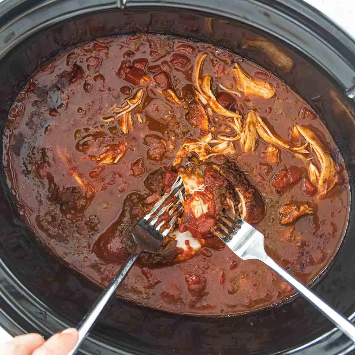 forks shredding chicken in crockpot