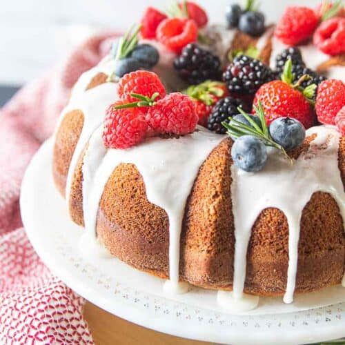 Bundt cake topped with berries on a serving dish