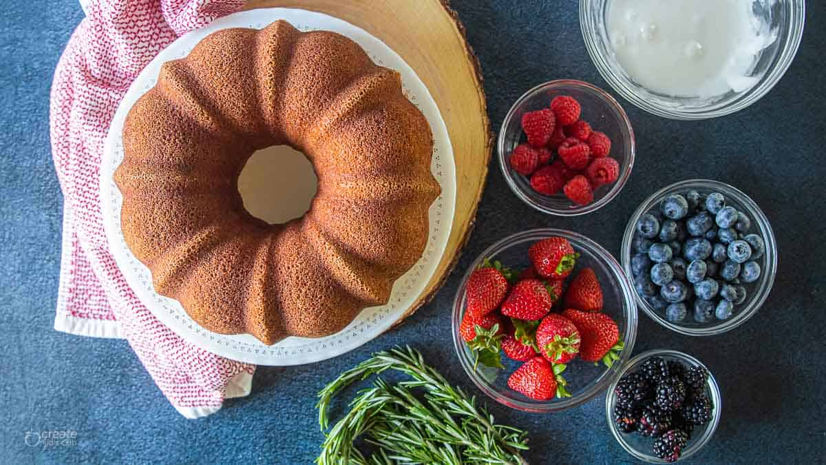 Bundt cake on a serving dish next to fresh berries
