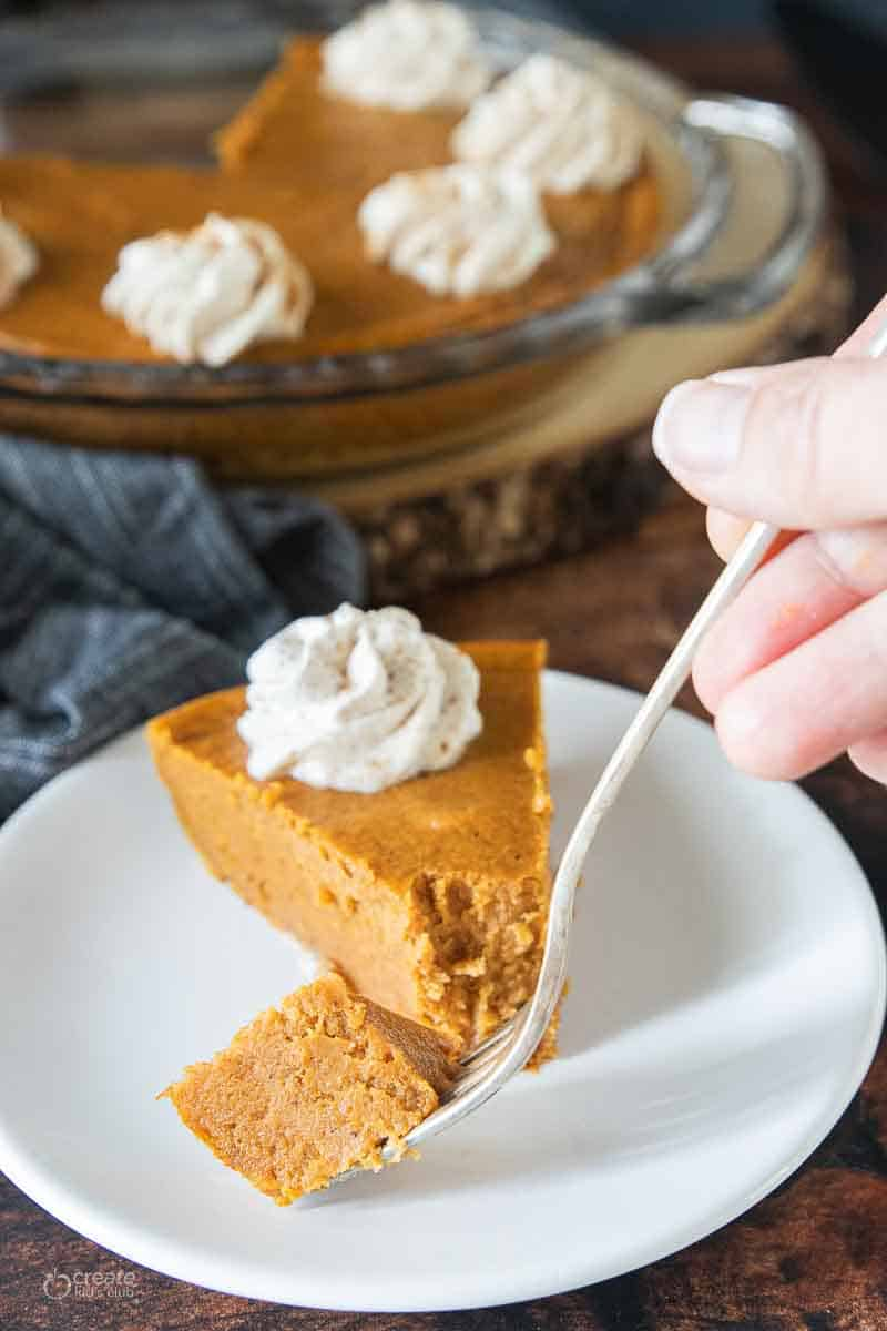 fork scooping a bite of pumpkin pie from plate