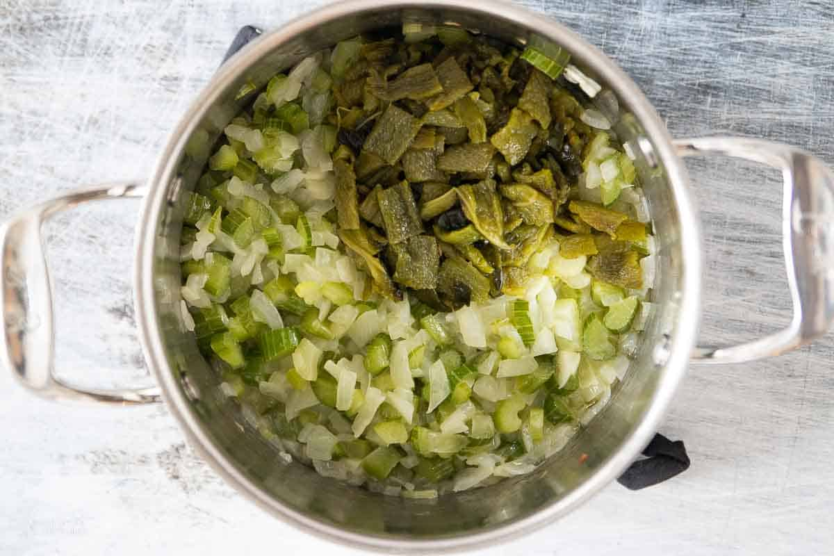 poblano peppers added to stock pot filled with diced onions and celery