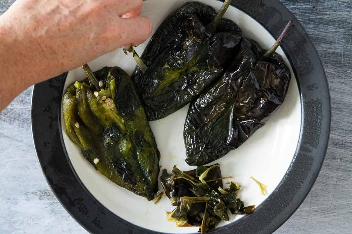 skin being removed from roasted poblano peppers