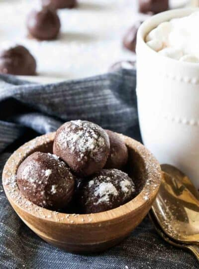 A square cropped photo of hot chocolate bombs in a bowl next to a mug.